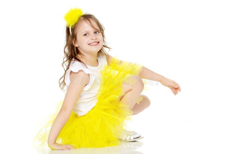 A menina em uma saia amarela senta-se no assoalho imagem de stock