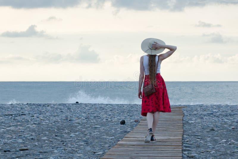 A menina em uma saia e em um chapéu vermelhos anda na plataforma na praia contra o contexto do mar e do céu fotos de stock royalty free