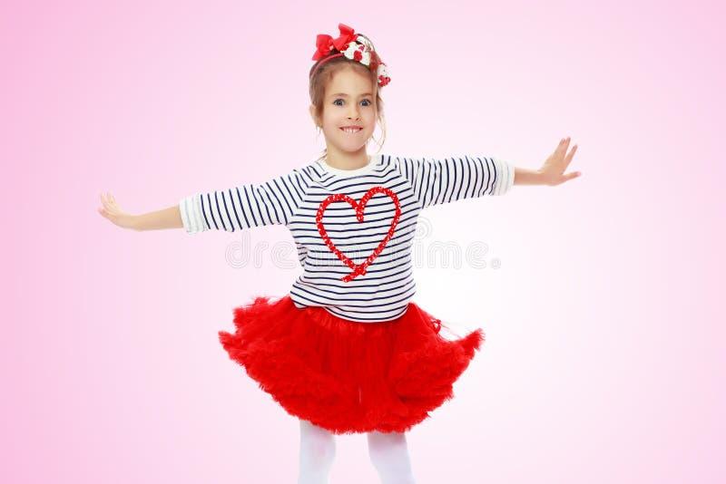 Menina em uma saia vermelha e curva em sua cabeça imagens de stock royalty free