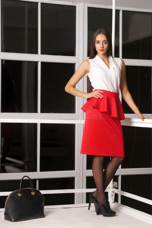 Menina em uma saia vermelha no salão da chegada no aeroporto imagem de stock royalty free