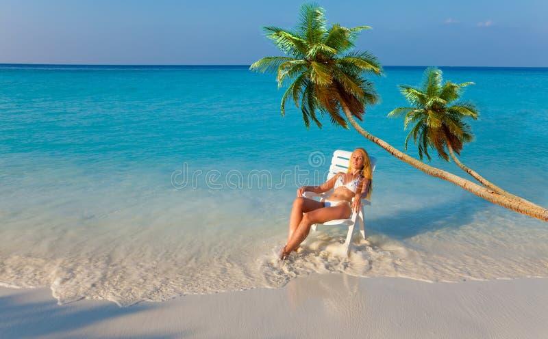 Menina em uma sala de estar do chaise no oceano sob palmeiras fotografia de stock