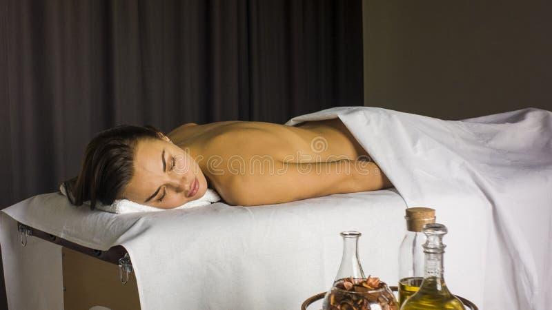 Menina em uma tabela da massagem pronta para uma massagem imagem de stock