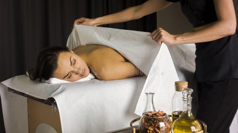 Menina em uma tabela da massagem pronta para uma massagem imagem de stock royalty free