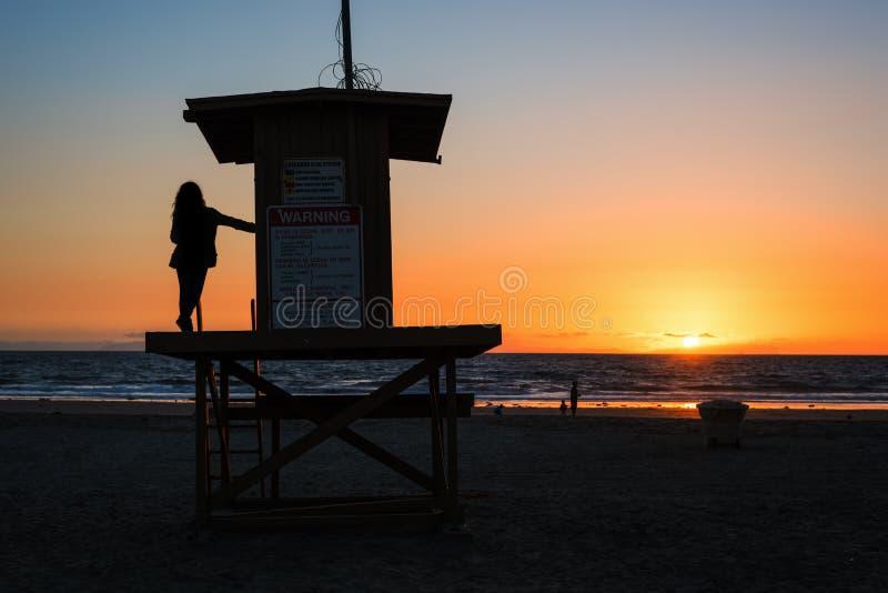 Menina em uma torre da salva-vidas na praia de Newport no por do sol foto de stock