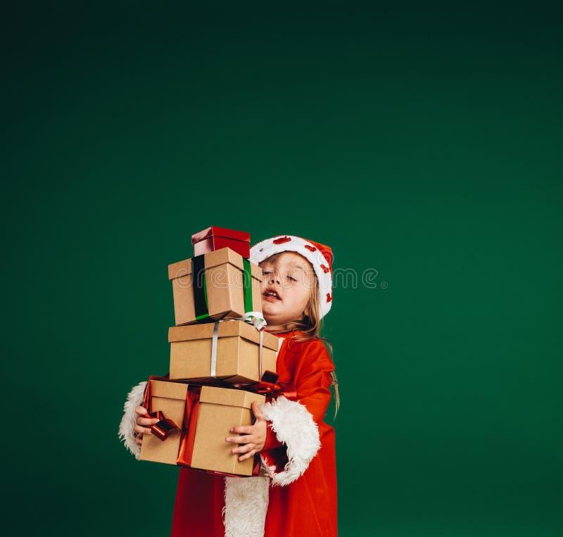 Menina em umas caixas de presente levando do vestido de Papai Noel imagens de stock