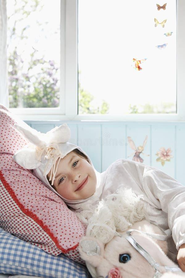 Menina em Unicorn Costume que encontra-se na cama imagens de stock