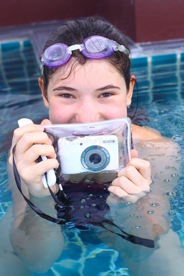 A menina em vidros de água fecha-se com câmera subaquática imagem de stock royalty free