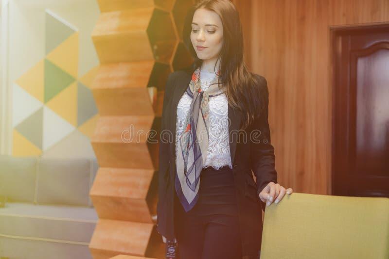 Menina emocional atrativa nova em um estilo do negócio em uma cadeira em um escritório ou em uma audiência moderna fotografia de stock