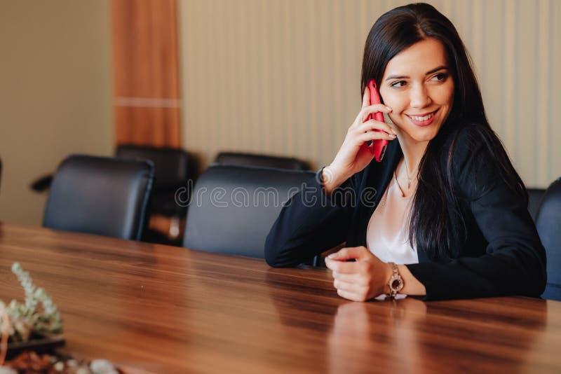 Menina emocional atrativa nova na roupa do estilo do neg?cio que senta-se na mesa com o telefone no escrit?rio ou na audi?ncia foto de stock royalty free