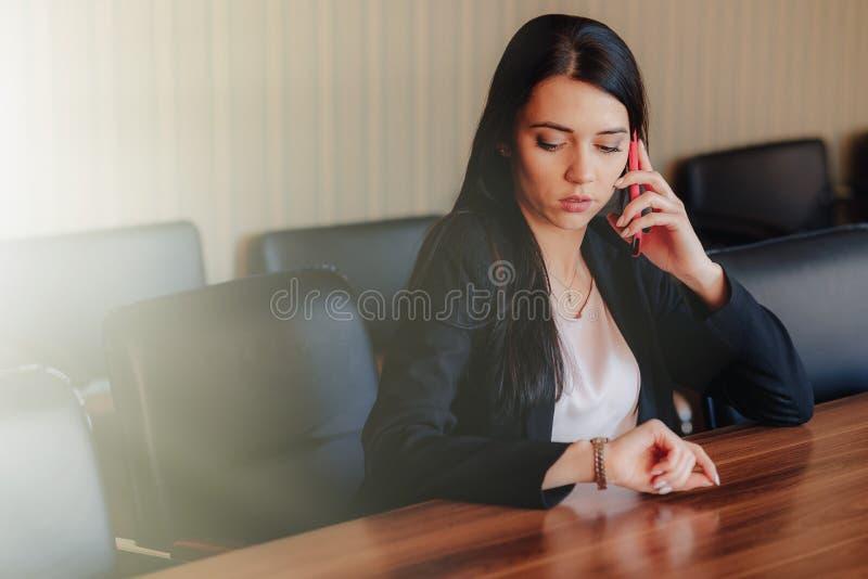Menina emocional atrativa nova na roupa do estilo do neg?cio que senta-se na mesa com o telefone no escrit?rio ou na audi?ncia fotos de stock