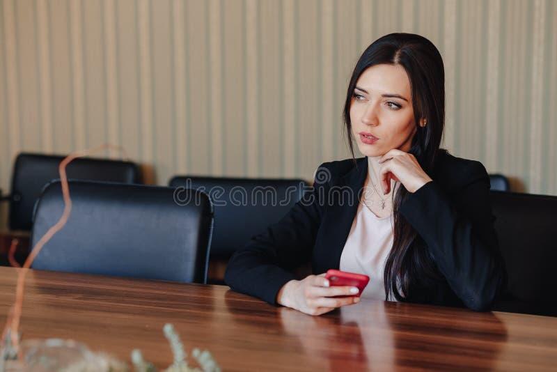 Menina emocional atrativa nova na roupa do estilo do neg?cio que senta-se na mesa com o telefone no escrit?rio ou na audi?ncia imagens de stock royalty free