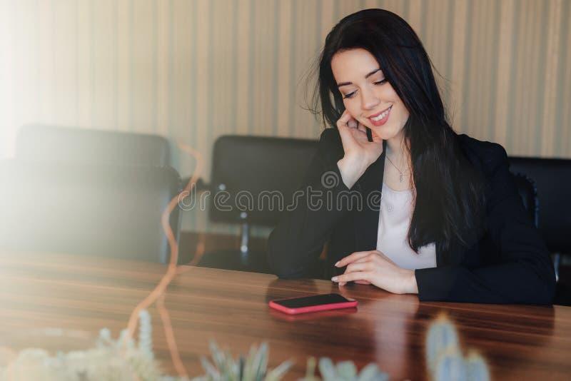 Menina emocional atrativa nova na roupa do estilo do neg?cio que senta-se na mesa com o telefone no escrit?rio ou na audi?ncia imagem de stock