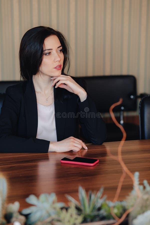 Menina emocional atrativa nova na roupa do estilo do neg?cio que senta-se na mesa com o telefone no escrit?rio ou na audi?ncia foto de stock