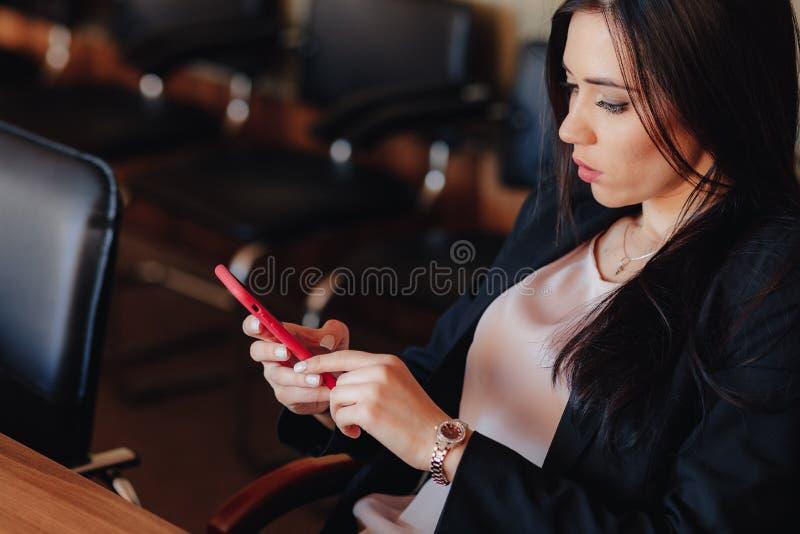 Menina emocional atrativa nova na roupa do estilo do neg?cio que senta-se na mesa com o telefone no escrit?rio ou na audi?ncia fotografia de stock royalty free