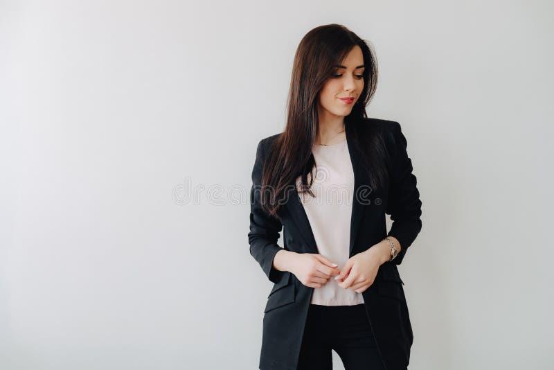 Menina emocional atrativa nova na roupa do neg?cio-estilo em um fundo branco liso em um escrit?rio ou em uma audi?ncia foto de stock