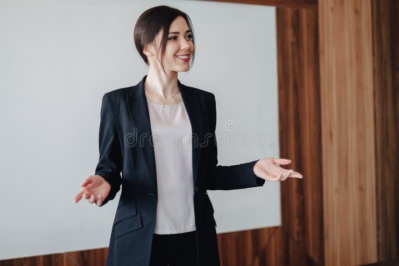 Menina emocional atrativa nova na roupa do neg?cio-estilo em um fundo branco liso em um escrit?rio ou em uma audi?ncia imagens de stock