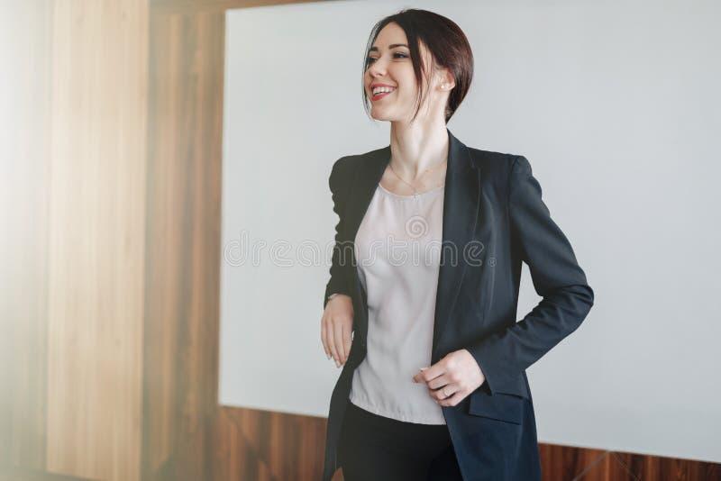 Menina emocional atrativa nova na roupa do neg?cio-estilo em um fundo branco liso em um escrit?rio ou em uma audi?ncia fotografia de stock