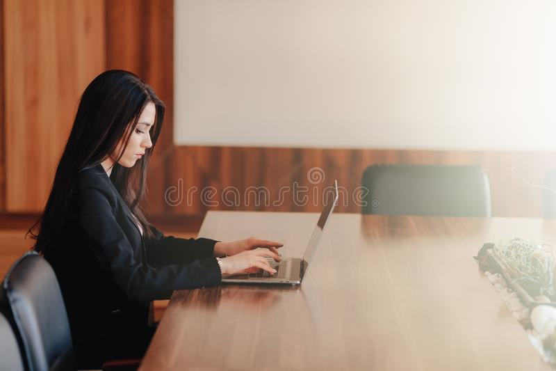 Menina emocional atrativa nova na roupa do neg?cio-estilo que senta-se em uma mesa em um port?til e em um telefone no escrit?rio  fotos de stock royalty free