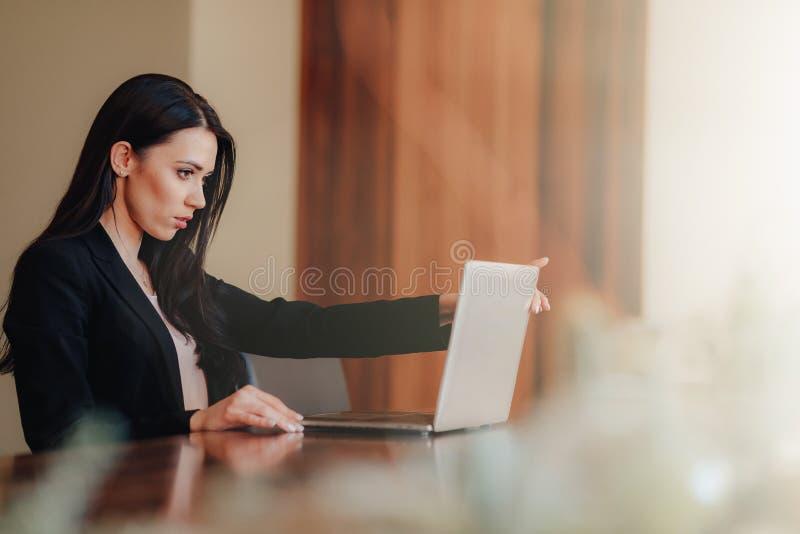 Menina emocional atrativa nova na roupa do neg?cio-estilo que senta-se em uma mesa em um port?til e em um telefone no escrit?rio  foto de stock