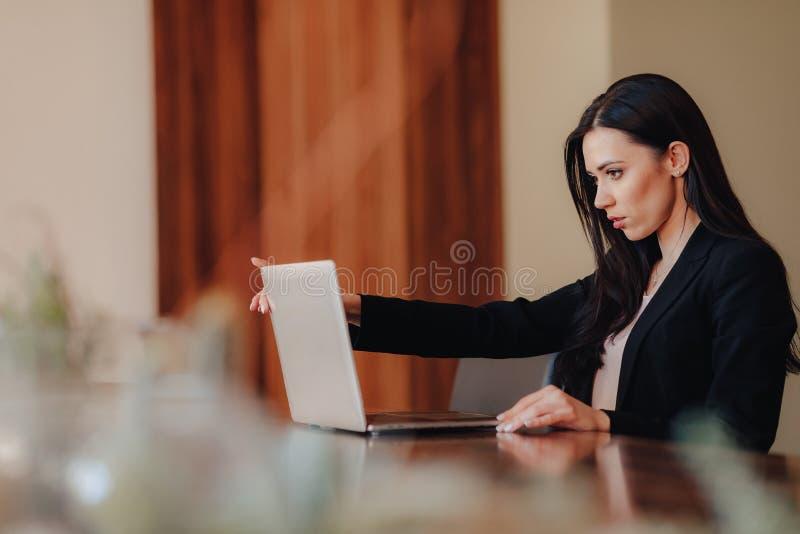 Menina emocional atrativa nova na roupa do neg?cio-estilo que senta-se em uma mesa em um port?til e em um telefone no escrit?rio  foto de stock royalty free