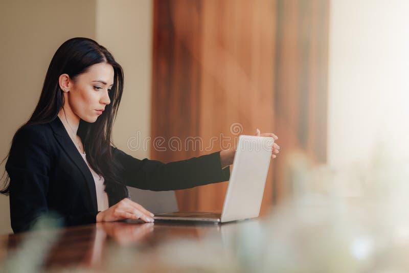 Menina emocional atrativa nova na roupa do neg?cio-estilo que senta-se em uma mesa em um port?til e em um telefone no escrit?rio  imagem de stock