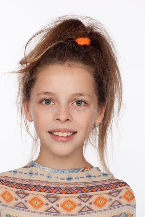 Menina emocional bonita dos anos de idade 8, com seu cabelo aumentado acima e em uma blusa com ornamento imagem de stock