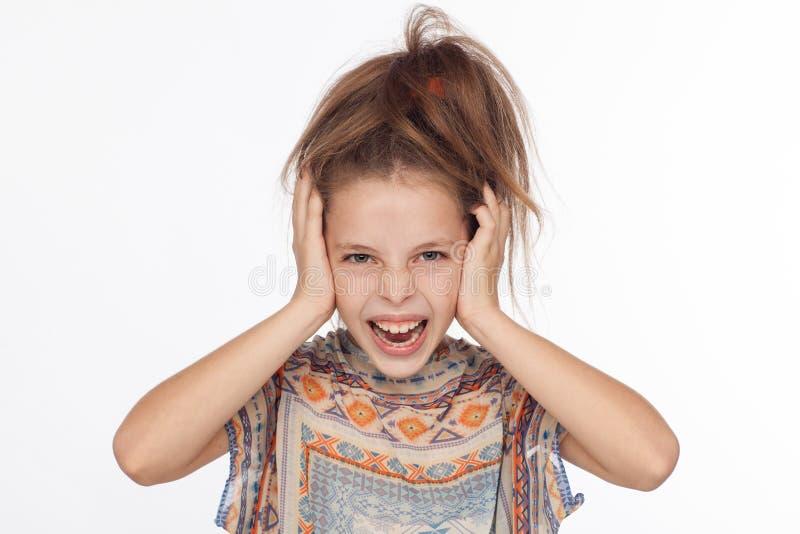 Menina emocional bonita dos anos de idade 8, com seu cabelo aumentado acima e em uma blusa com ornamento fotografia de stock royalty free