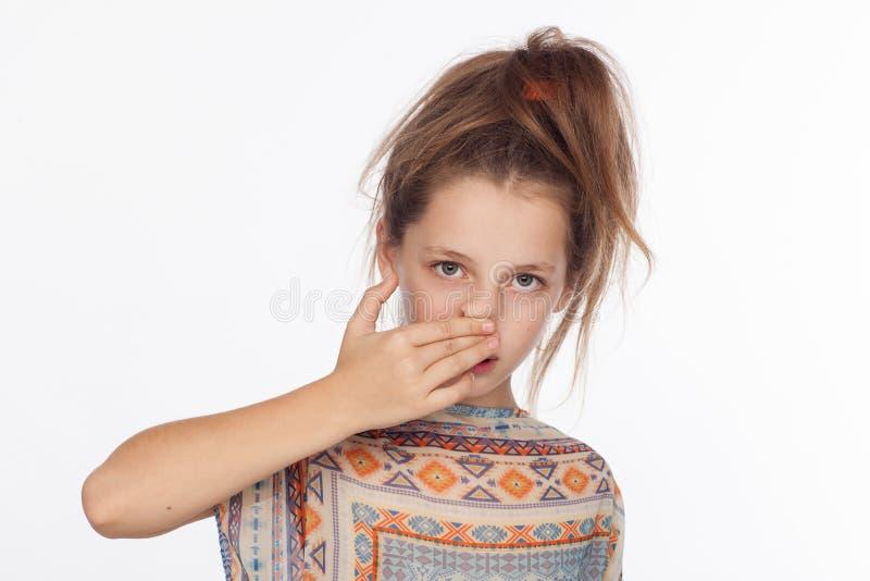 Menina emocional bonita dos anos de idade 8, com seu cabelo aumentado acima e em uma blusa com ornamento imagem de stock royalty free