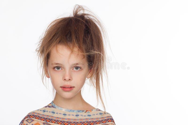 Menina emocional bonita dos anos de idade 8, com seu cabelo aumentado acima e em uma blusa com ornamento imagens de stock royalty free