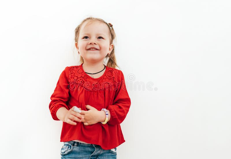 Menina emocional de sorriso feliz na blusa vermelha no fundo branco da parede fotografia de stock