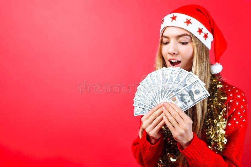 Menina emocional em uma camiseta e em um chapéu vermelhos de Santa Claus, na admiração que guarda o dinheiro em um fundo vermelho foto de stock