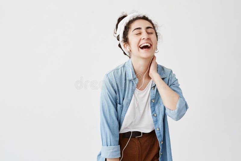 A menina emocional feliz expressivo com cabelo escuro e encaracolado no bolo, escuta a música nos fones de ouvido, aprecia melodi fotografia de stock