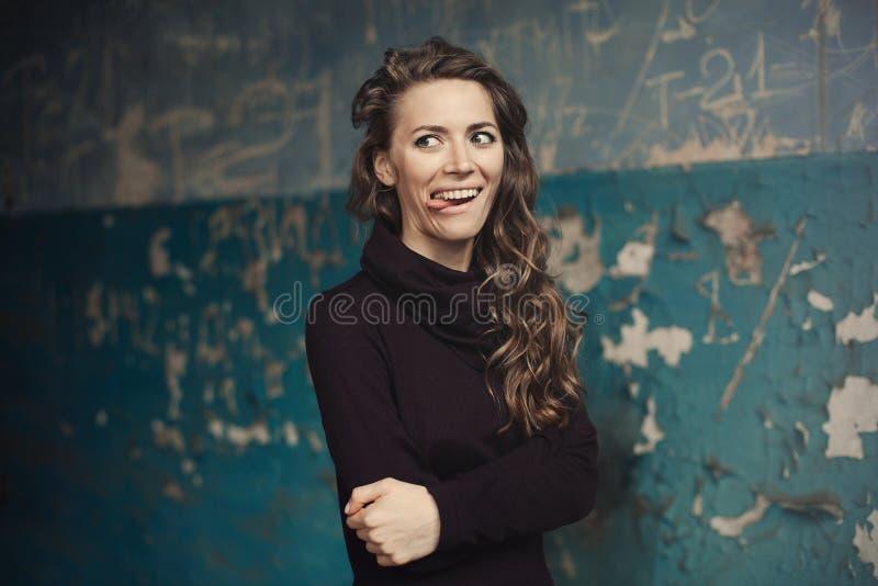 Menina emocional O modelo moderno bonito mostra a língua o moderno positivo da mulher Emoções na face foto de stock