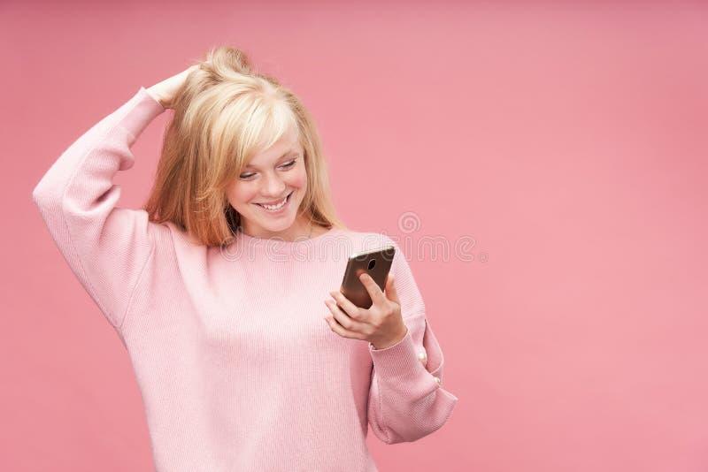 Menina emocional que olha o telefone O louro bonito novo olha admiringly no smartphone que guarda sua mão a sua cabeça feliz fotos de stock