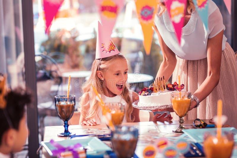Menina emocional que sente entusiasmado ao olhar seu bolo de aniversário fotos de stock royalty free