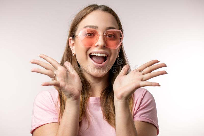 Menina emocional surpreendida do moderno com as mãos abertas que olham a câmera imagens de stock royalty free