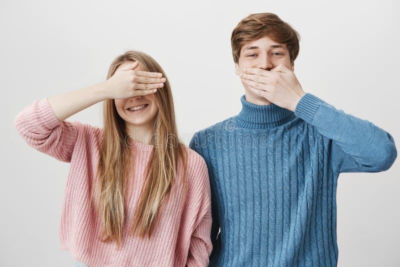 A menina encantador alegre na camiseta cor-de-rosa sorri felizmente com cintas e fecha os olhos, quando o menino ao lado dela fec imagem de stock royalty free