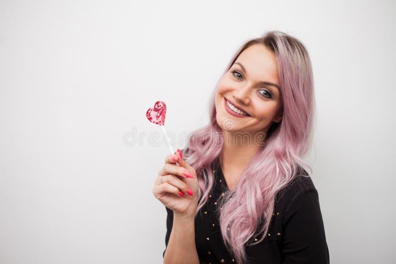 Menina encantador bonita com um pirulito sob a forma do coração Retrato de uma jovem mulher com cabelo cor-de-rosa e os doces cor imagens de stock royalty free