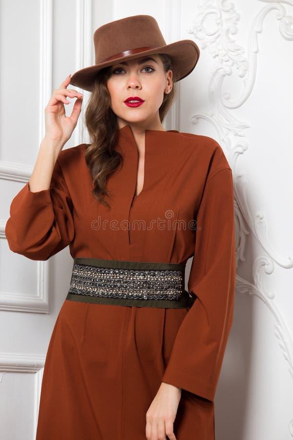 A menina encantador elegante vestida no vestido marrom com uma correia larga e um chapéu marrom levanta contra uma parede branca  imagens de stock