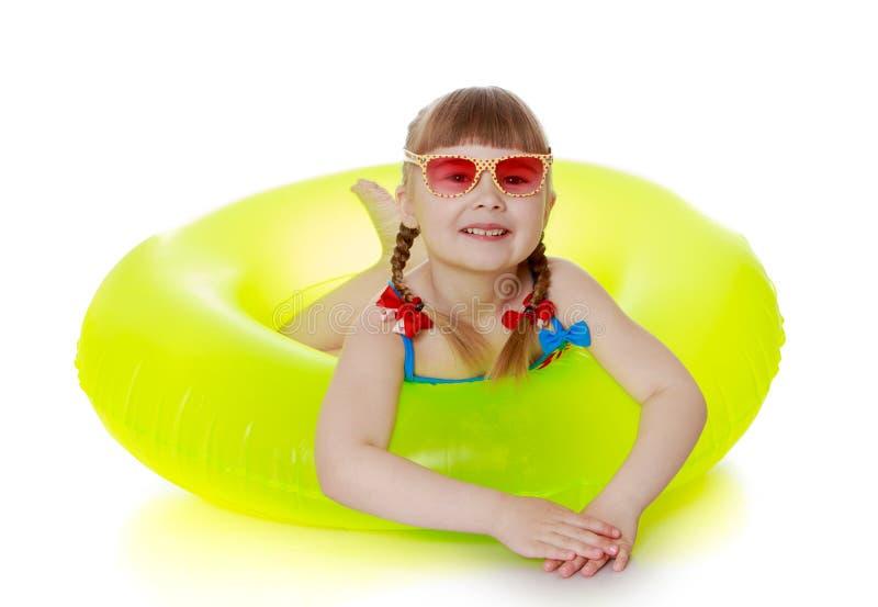 Menina encantador em um roupa de banho, em óculos de sol e em amarelo imagens de stock royalty free
