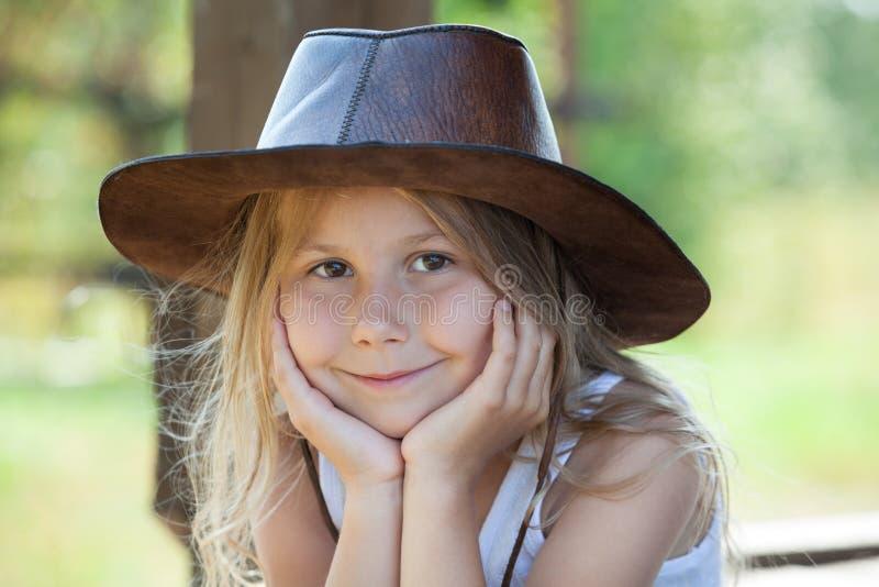 Menina encantador no retrato de couro do chapéu de vaqueiro, cabelo louro, olhos marrons fotos de stock