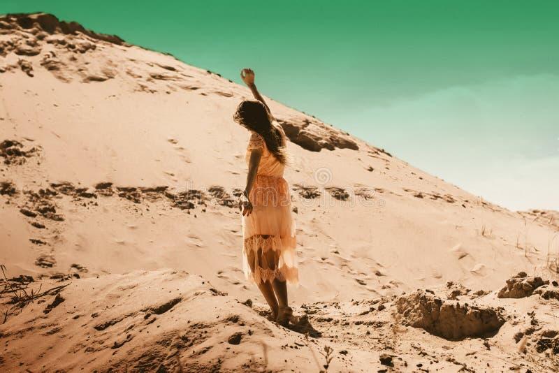Menina encantador no vestido cor-de-rosa no deserto foto de stock