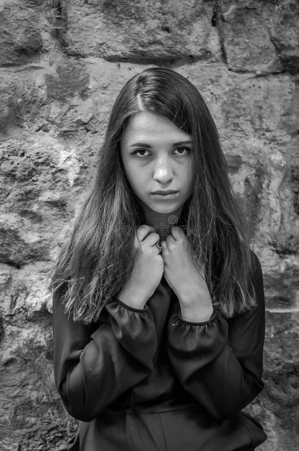 Menina encantador nova do adolescente com o cabelo escuro longo que está perto das ruínas da fortaleza antiga do castelo com uma  fotos de stock