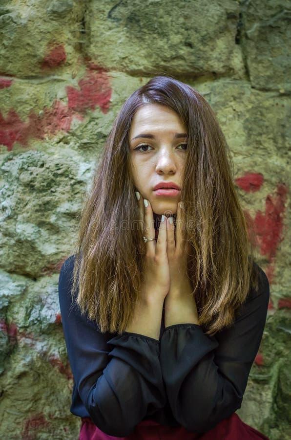 Menina encantador nova do adolescente com o cabelo escuro longo que está perto das ruínas da fortaleza antiga do castelo com uma  imagem de stock