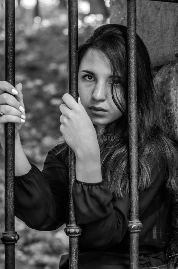 Menina encantador nova do adolescente com o cabelo escuro longo que senta-se atrás das barras em uma prisão na fortaleza velha do fotografia de stock royalty free