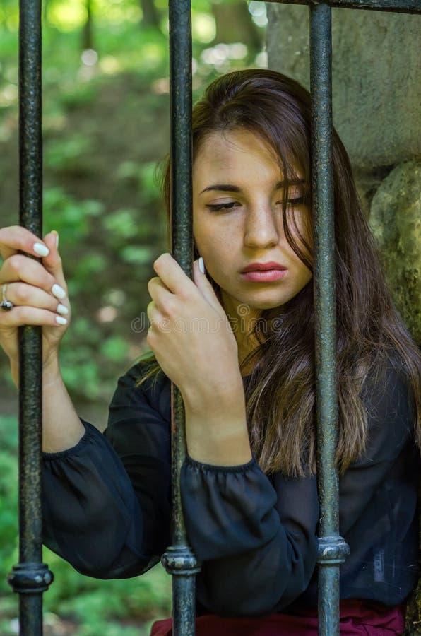 Menina encantador nova do adolescente com o cabelo escuro longo que senta-se atrás das barras em uma prisão na fortaleza velha do foto de stock royalty free