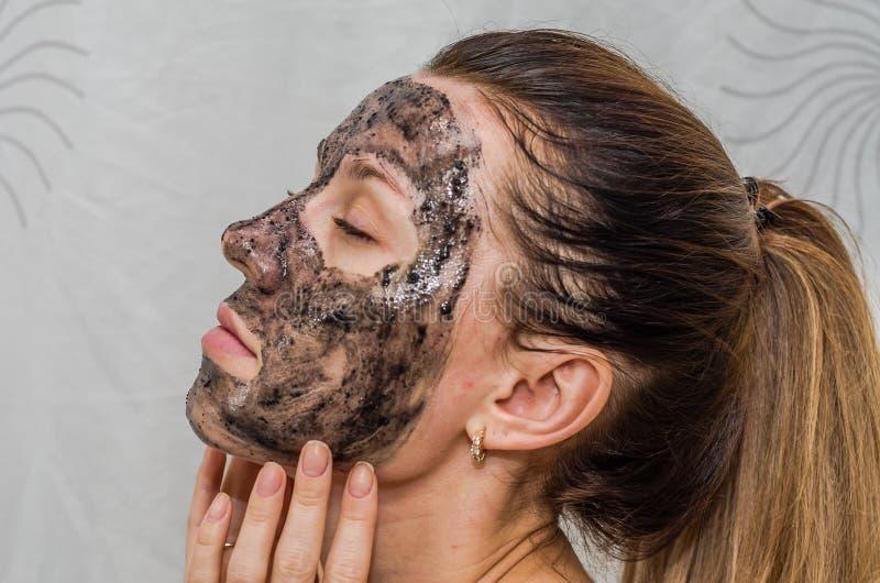A menina encantador nova faz uma máscara preta do carvão vegetal em sua cara foto de stock royalty free