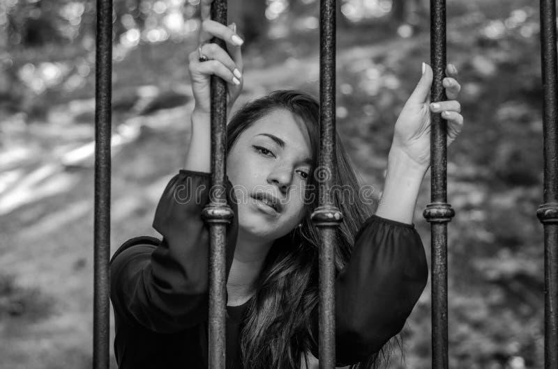 A menina encantador nova o adolescente com o cabelo longo que senta-se atrás das barras no prisioneiro da prisão em uma cadeia me fotografia de stock