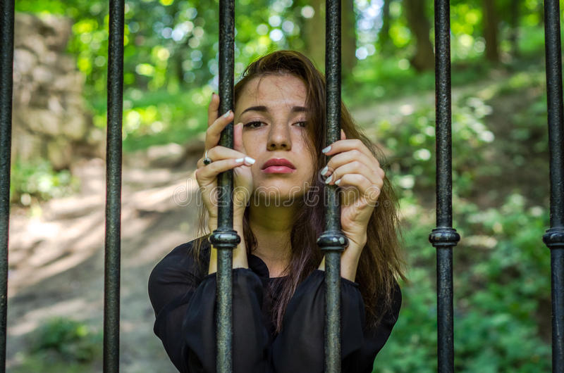 A menina encantador nova o adolescente com o cabelo longo que senta-se atrás das barras no prisioneiro da prisão em uma cadeia me imagem de stock