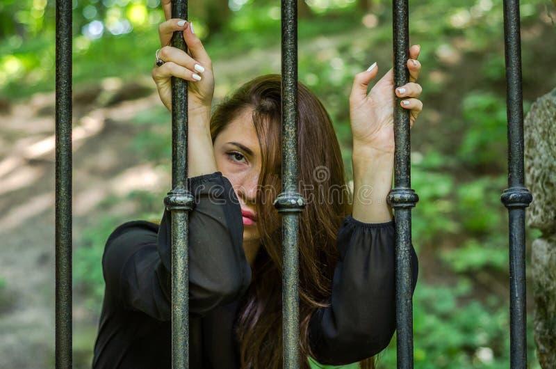 A menina encantador nova o adolescente com o cabelo longo que senta-se atrás das barras no prisioneiro da prisão em uma cadeia me fotos de stock royalty free